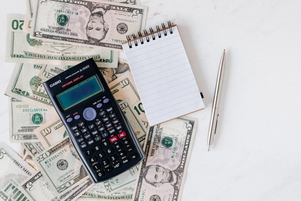 Fiis de Papel: Imagem com notas de doláres, calculadora científica, bloco de notas sobre uma mesa branca.