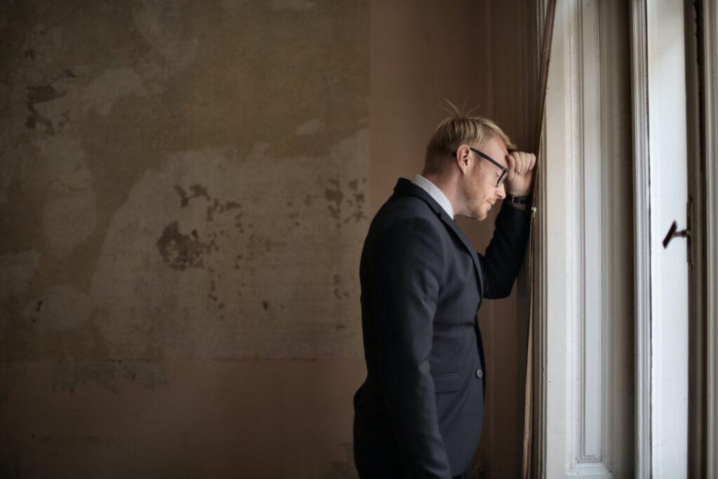 Abrir conta em corretora: Vemos um homem loiro de óculos e terno com o punho cerrado tocando a testa e a parede e de olhos cerrados.