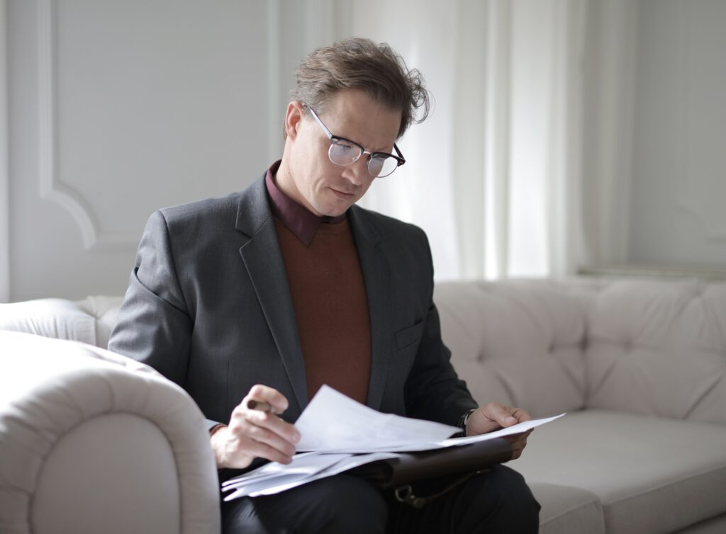 Abrir conta em corretora: Vemos um homem de óculos com traje social enquanto folia documentos em um sofá.