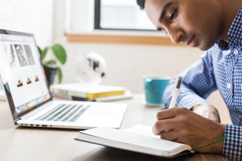 Como investir em Fiis: Vemos um homem de camisa quadriculada segurando uma caneta e anotando em um caderno em frente a um laptop.