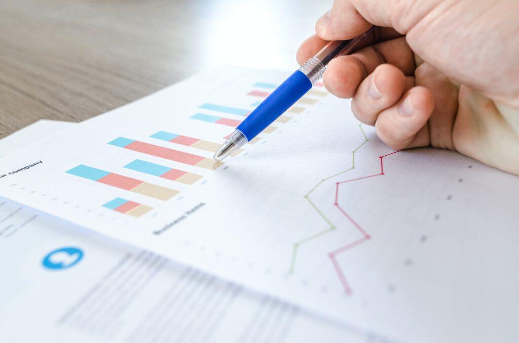 Como investir em Fiis: Vemos uma caneta azul e uma mão que a segura sobre uma folha contendo gráficos e análises.
