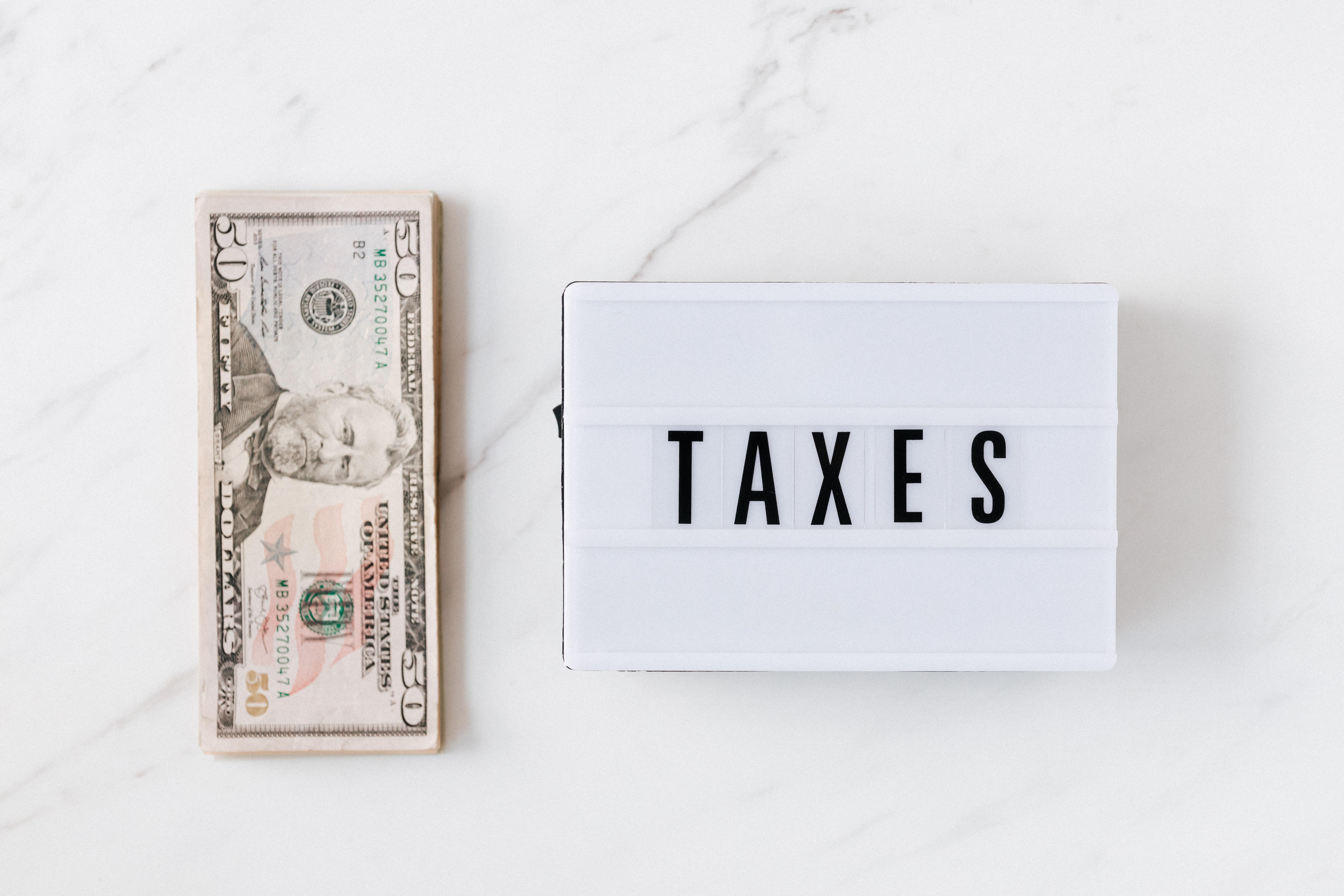 """Imposto de Renda dos Fiis: Vemos um malote de dólares e ao lado um pequeno letreiro com a palavra """"Taxes"""""""