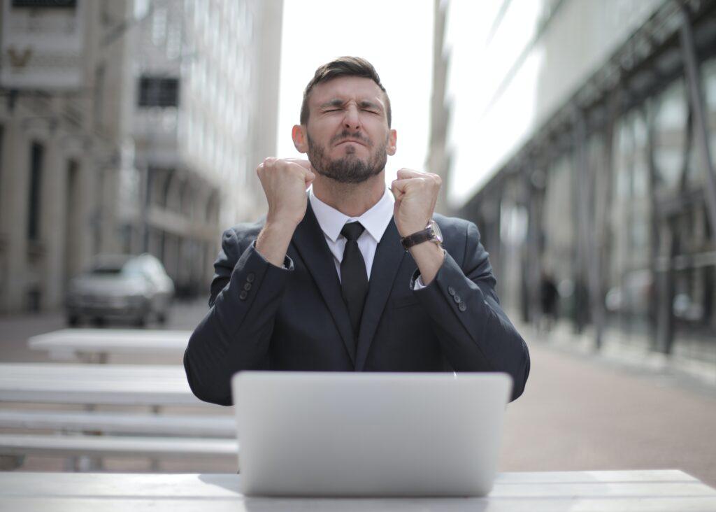 Investir em Fiis: Vemos um homem de terno comemorando de olhos fechados de frente para um laptop.
