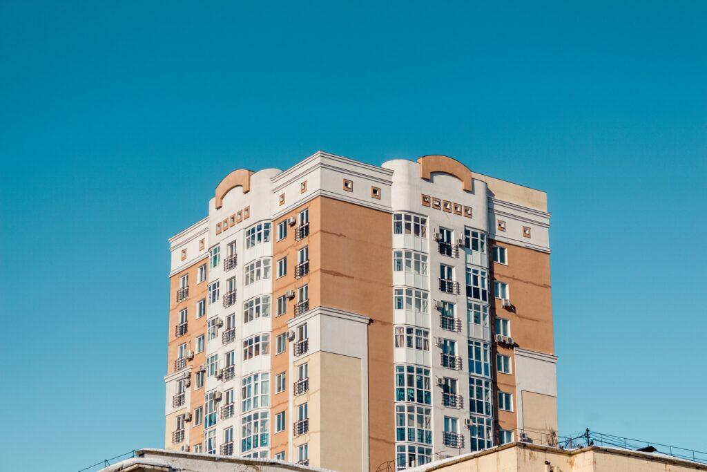 Investir Imóveis: Vemos uma construção com várias janelas e um céu azul.