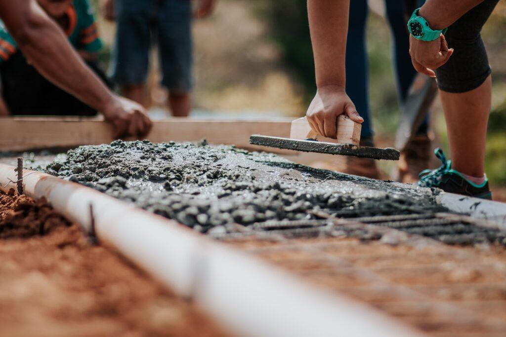 Fundo de tijolo: homens trabalhando na fundação de um imóvel.