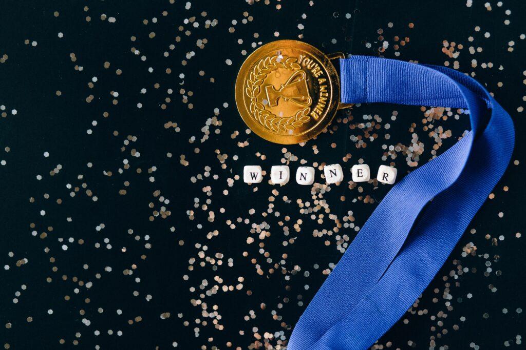 """home broker: Vemos uma medalha de ouro com uma fita azul, com um troféu estampado e com os seguintes dizeres: """"You're the winner"""", que significa """"Você é o vencedor"""""""