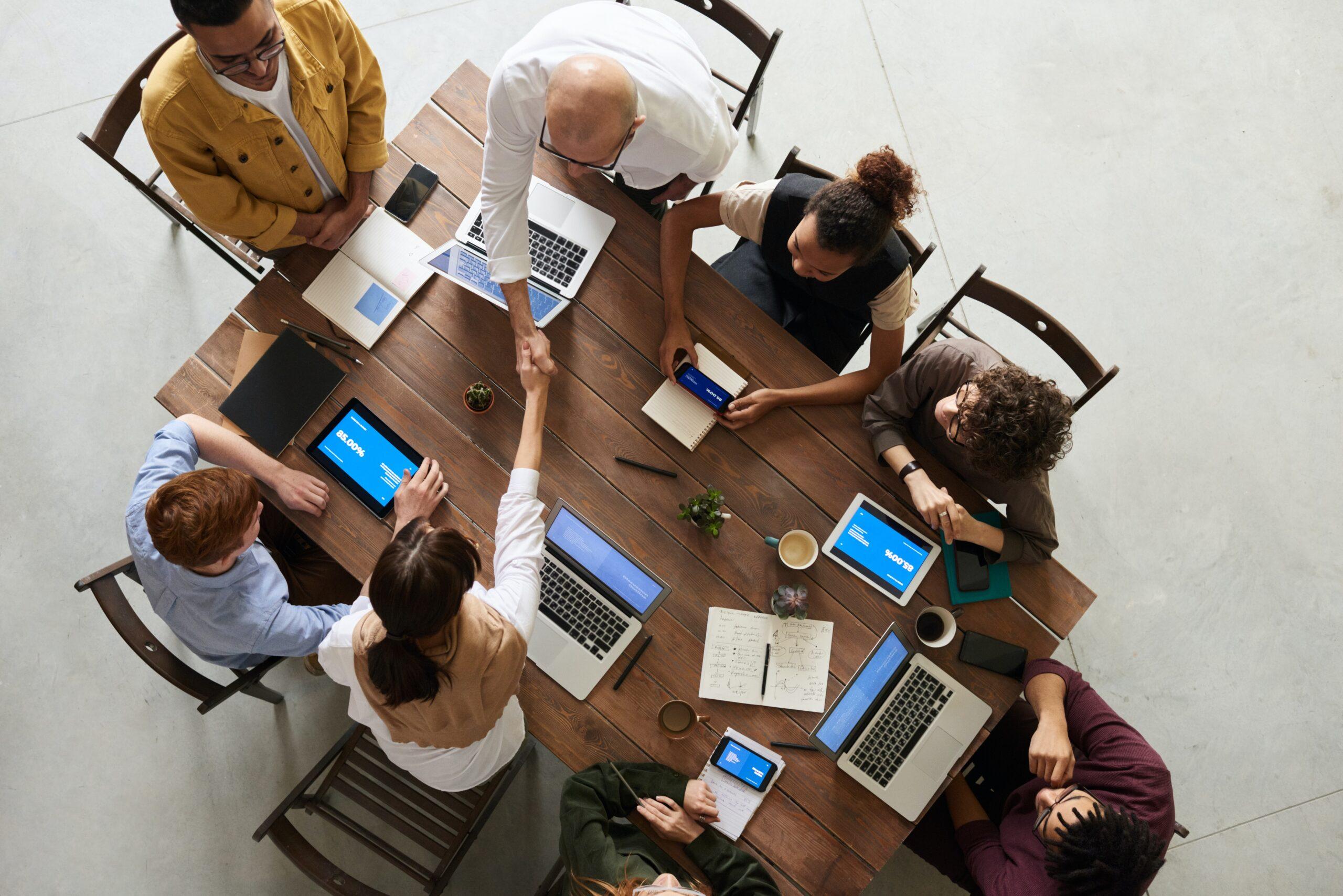 Vemos pessoas em reunião com laptops e cadernos enquanto duas dessas pessoas dão um aperto de mão, remetendo ao investidor profissional.