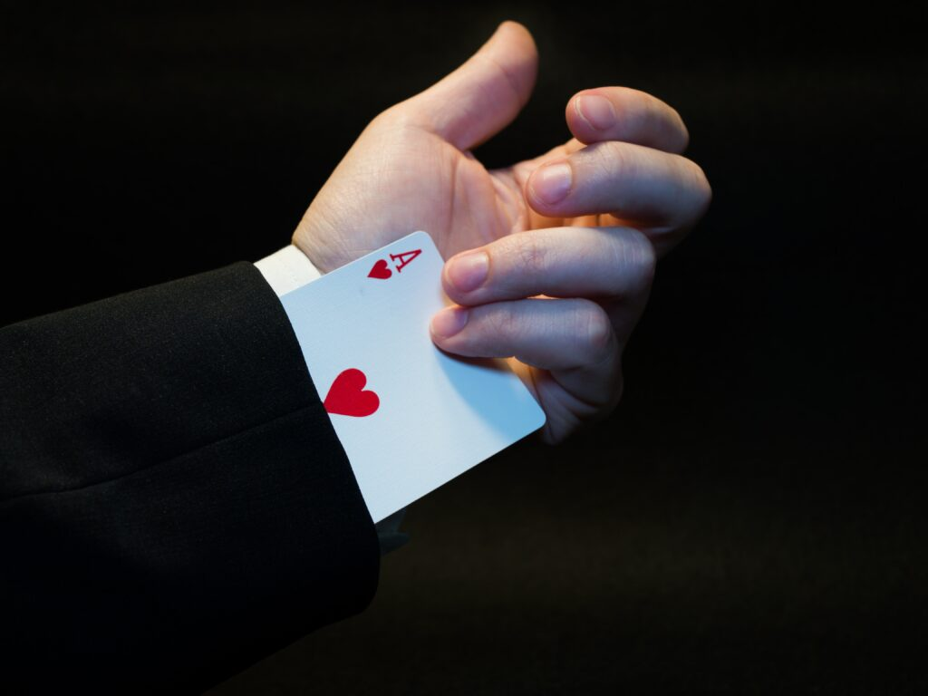 """Vemos uma carta de baralho """"Ás de copas"""" sendo retirada de uma manga de terno, remetendo ao investidor profissional."""