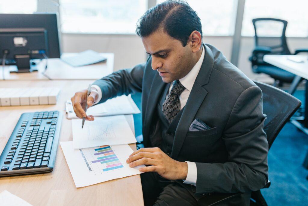 Securitização: Vemos um homem com traje executivo e analisando alguns gráficos