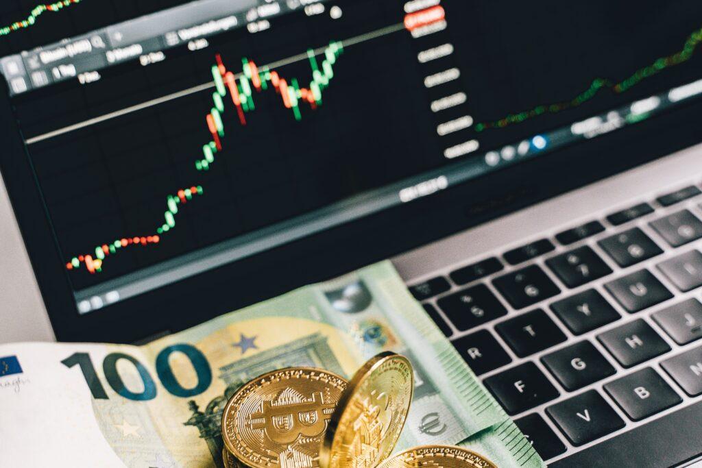Vemos dinheiro sobre um teclado de laptop e um monitor mostrando um gráfico de home broker, fazendo referência às ações.