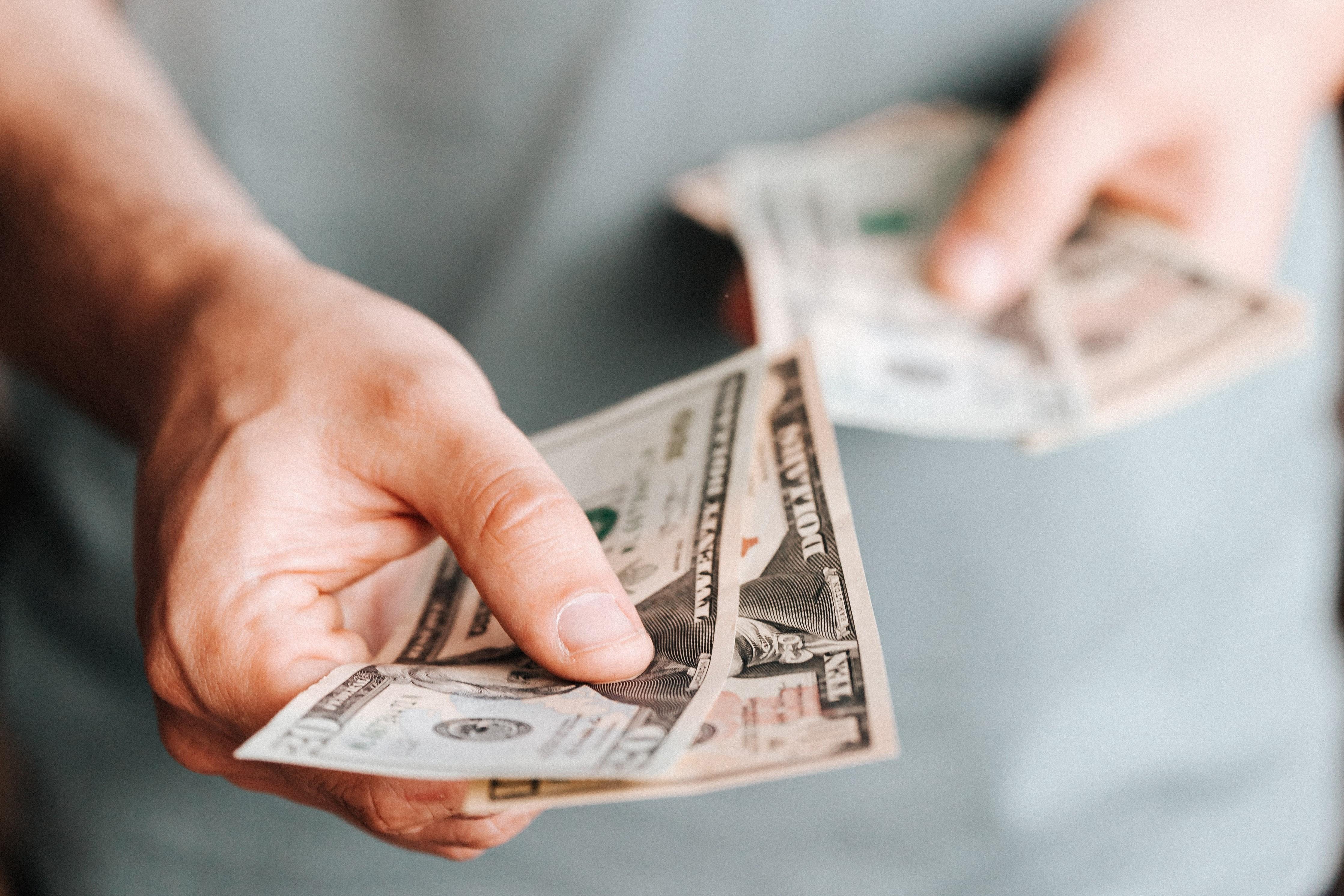 Vemos um homem mostrando notas de dólares, fazendo referência às ações.