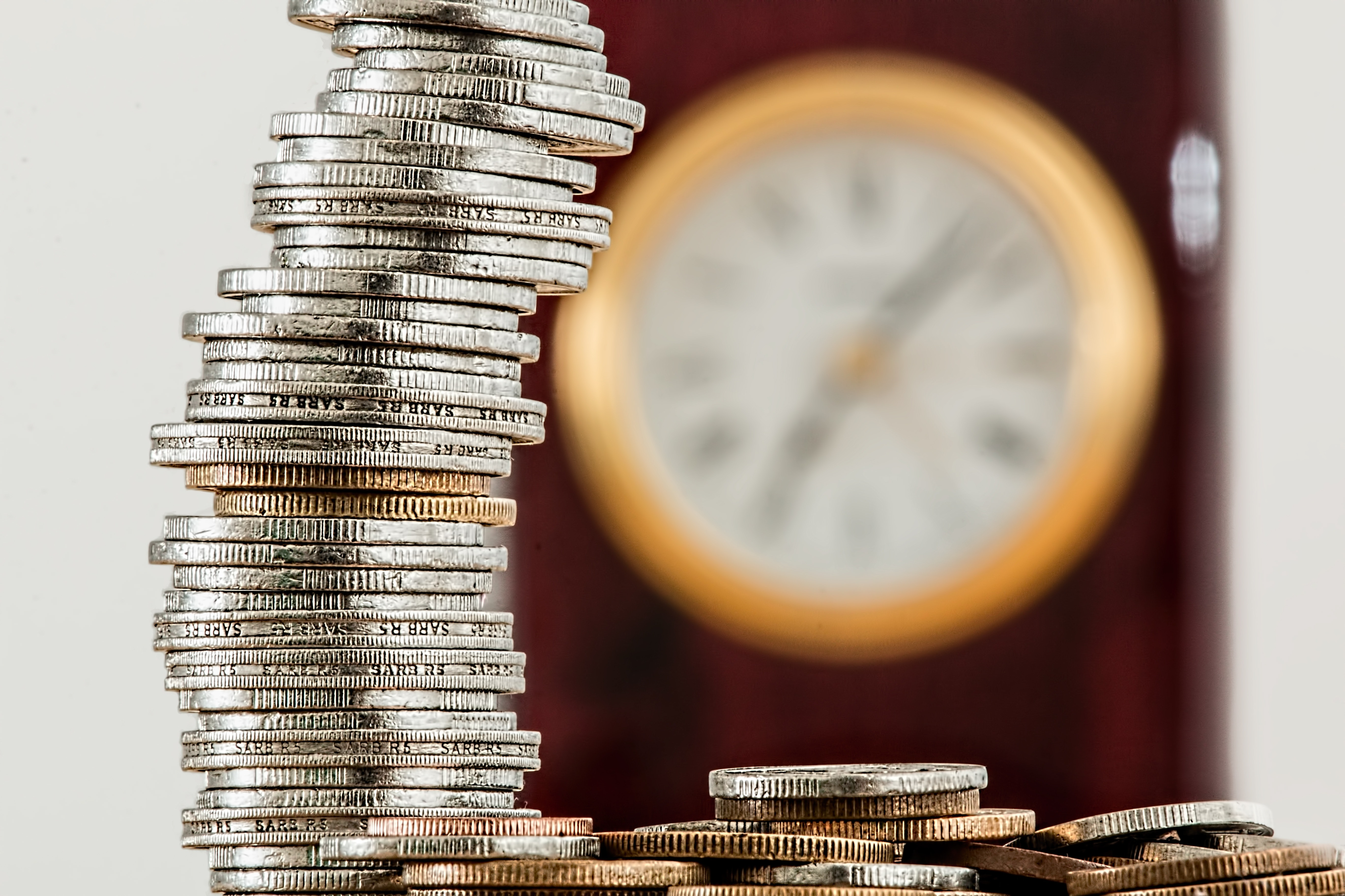 Vemos uma pilha de moedas e no fundo um relógio desfocado, remetendo a corretagem.