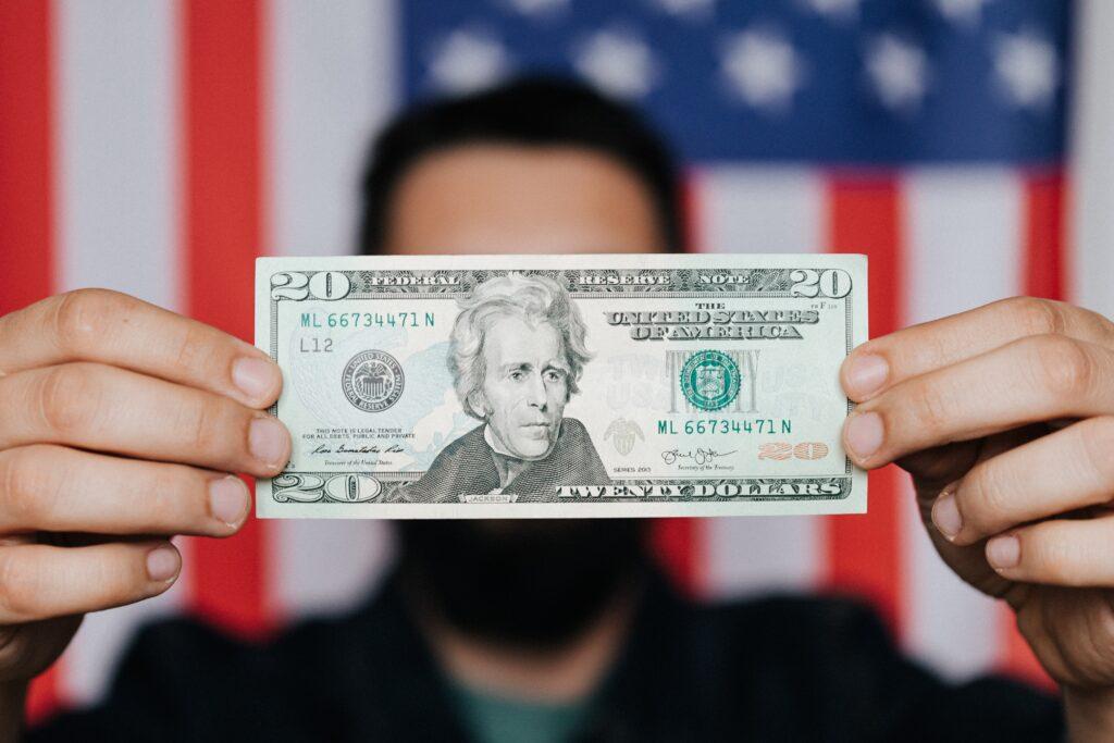 Um homem segurando uma nota de 20 doláres, fazendo referência a subscrição