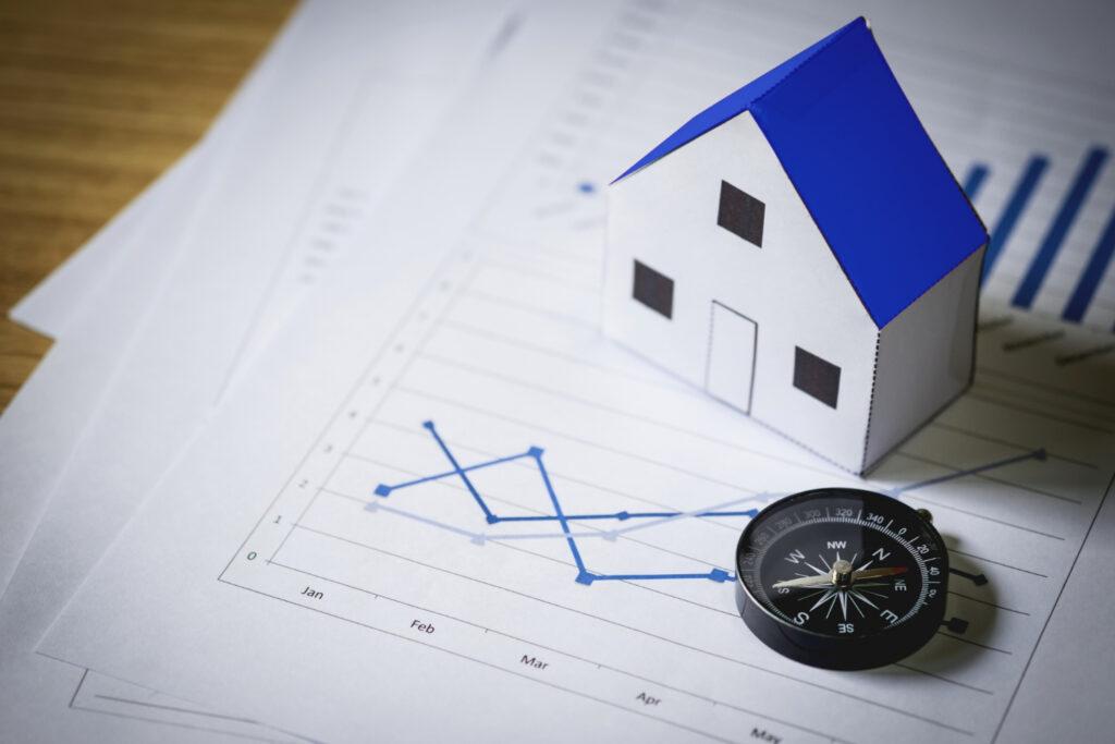 Várias folhas com gráficos desenhados estão sobre uma mesa. Em cima delas, uma casa e uma bússola, que mostram a importância da personalização e da localização no built to suit