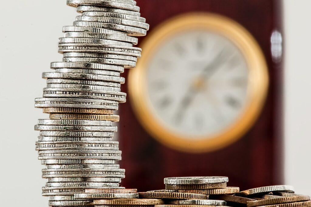 uma pilha de moedas aparece em destaque. Na mesa em que ela está, tem várias moedas espalhadas. Ao fundo e de forma desfocada, tem um relógio de parede, representando os ganhos com o CDB