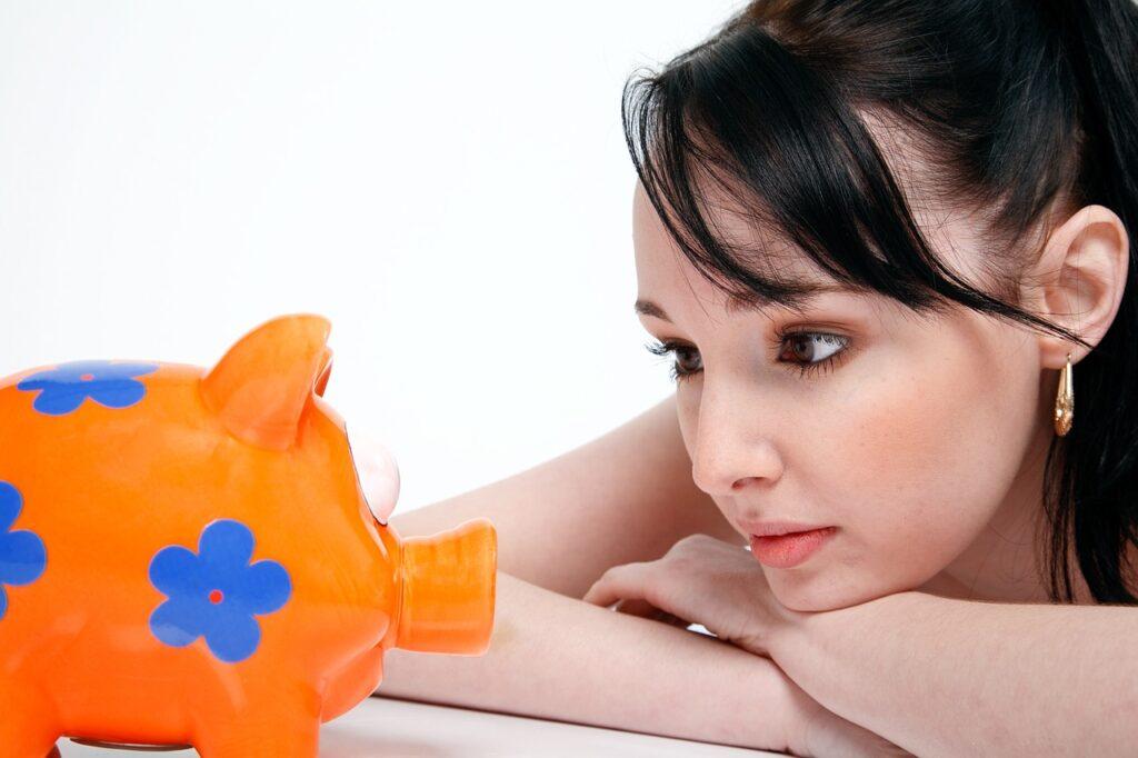 uma mulher que quer investir em CDB aparece olhando para um cofre em formato de porquinho, na cor laranja com flor azul.