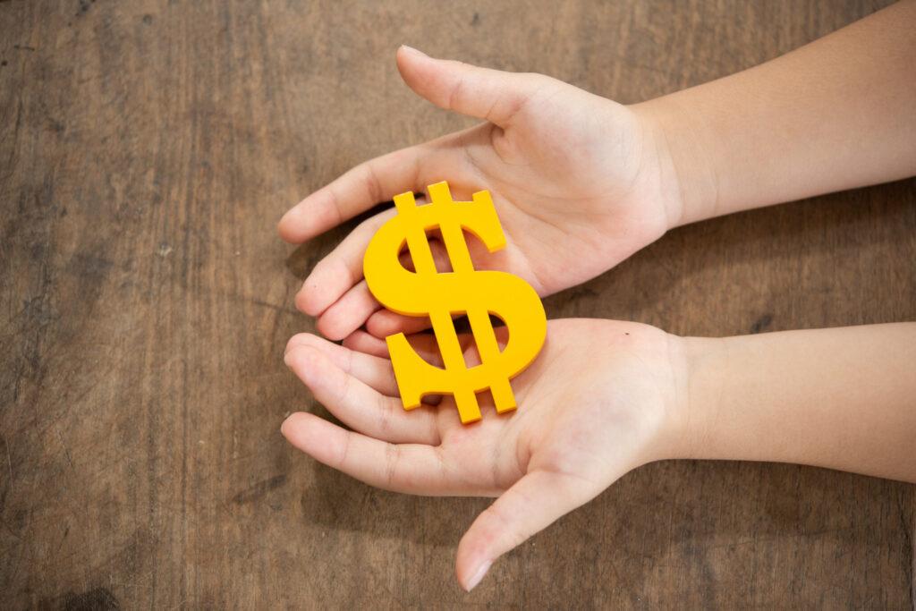 Duas mãos seguram um cifrão, representando como ganhar dinheiro com CDB