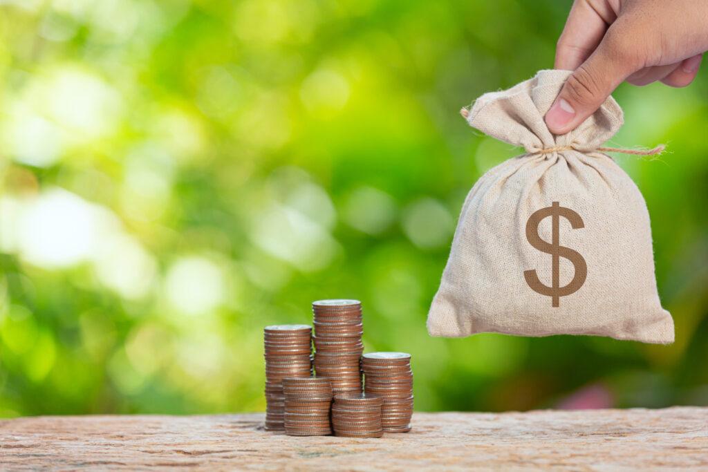 5 pilhas de moedas estão sobre uma mesa e uma mão coloca ao lado um saco com um cifrão, representando o dinheiro coberto pelo FGC nas aplicações financeiras