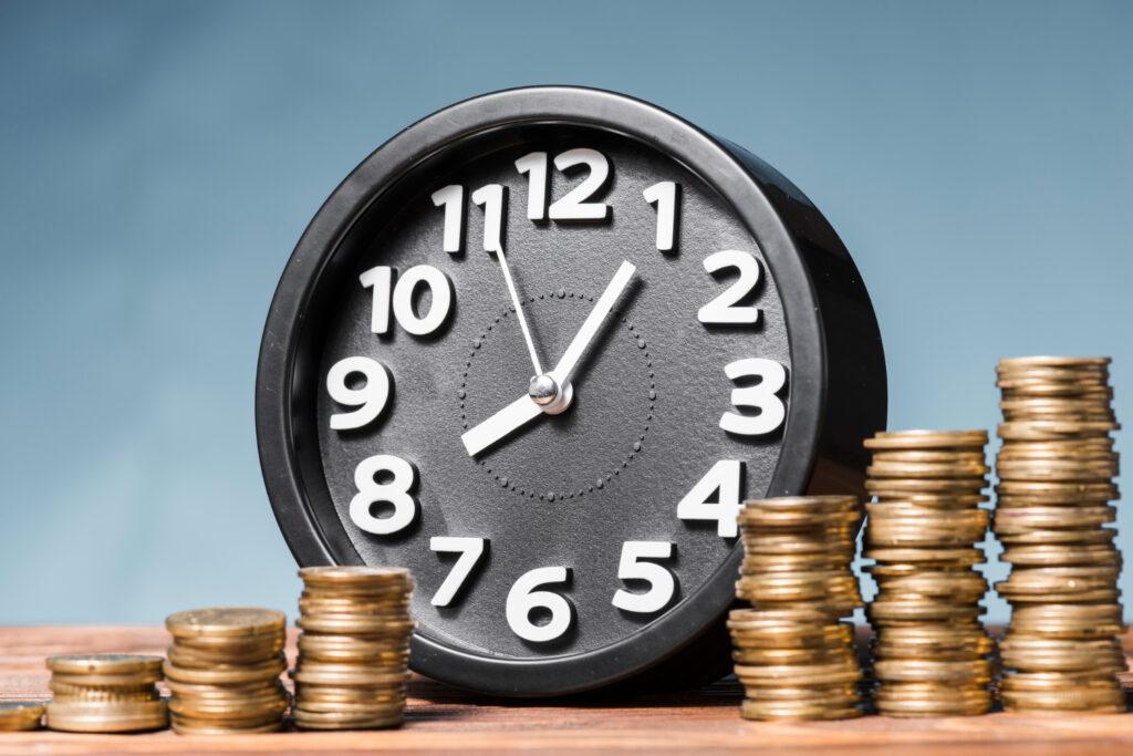 Um relógio de parede preto aparece com várias pilhas de moedas em sua frente, mostrando os fundos de investimento de curto e longo prazo