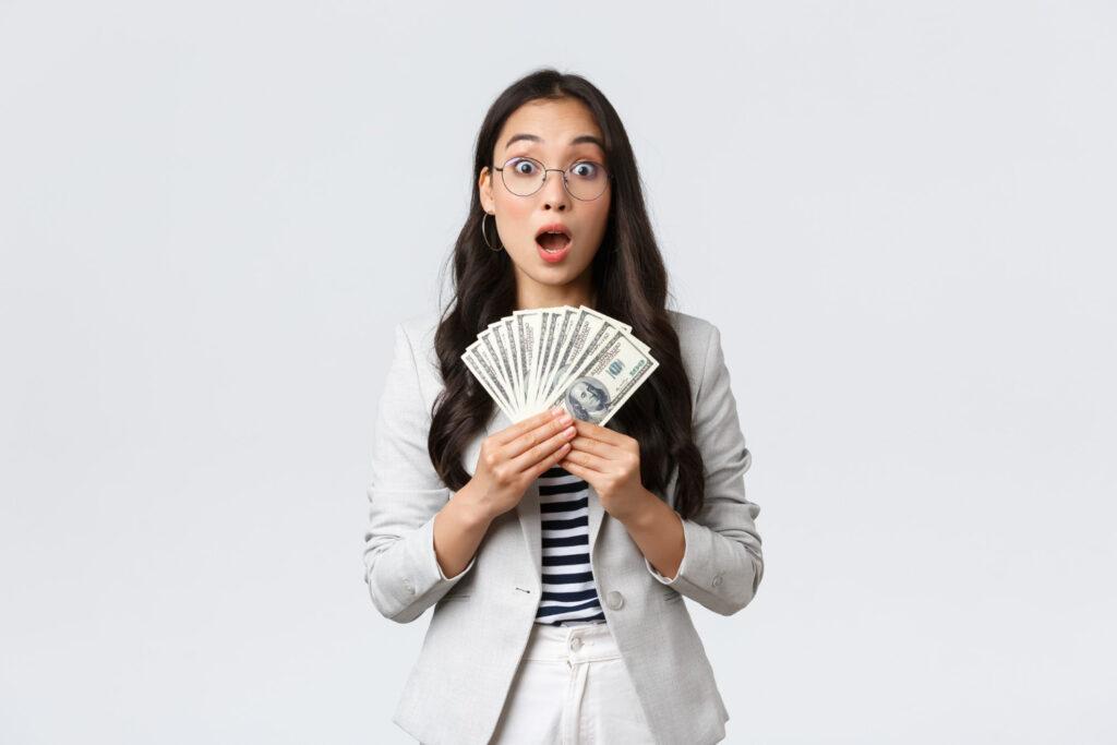 Mulher aparece com cara de surpresa e segura várias notas de dólar na mão, em formato de leque. Isso representa os ganhos proporcionais dos cotistas de fundos de investimento