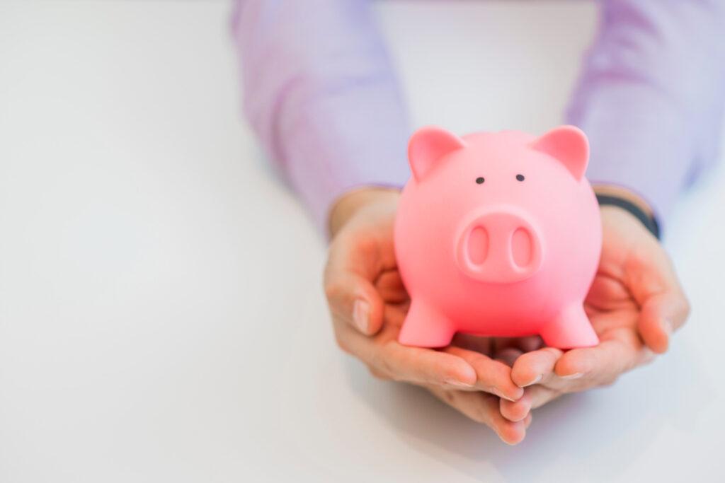 Duas mãos untas seguram um cofrinho em formato de porco, representando os ganhos com os fundos de investimento