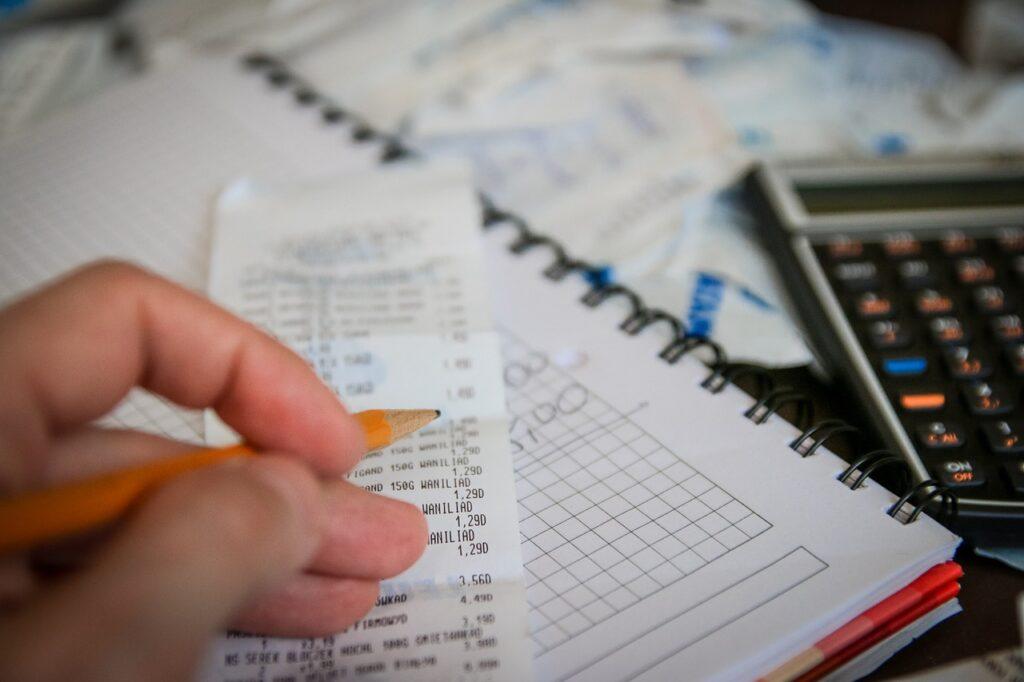 Uma mão segura um lápis. Embaixo dela há um cupom fiscal, um caderno com números escritos, uma calculadora e várias contas, representando o impacto do IGPM no dia a dia