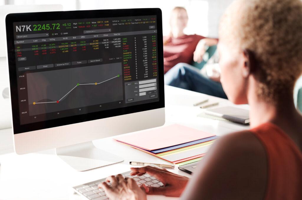 uma mulher sentada de frente para o computador analisa as ações de uma empresa que fez IPO