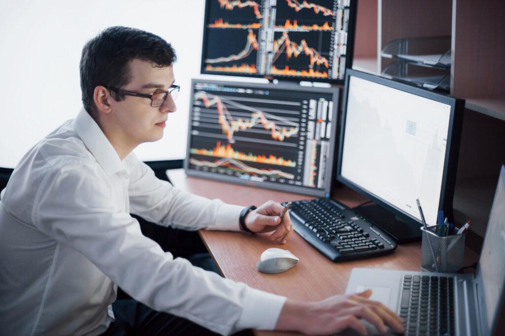 Homem está sentado em frente a um computador e tem mais dois monitores ao lado. Nas telas, aparecem gráficos da renda variável e o home broker que ele usa para negociar ativos