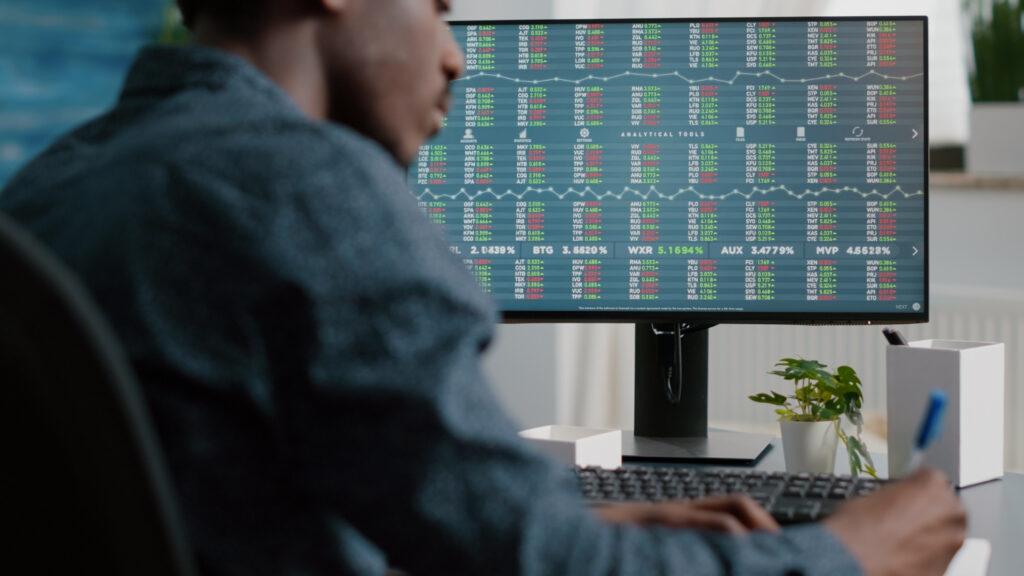 homem está mexendo em um computador e há várias informações de investimento em renda variável na tela