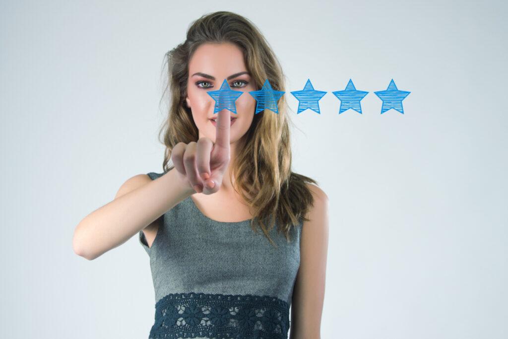 uma mulher aparece clicando em uma de 5 estrelas que estão desenhadas em azul na sua frente. As estrelas representam o bom desempenho sobre o qual incide a taxa de performance