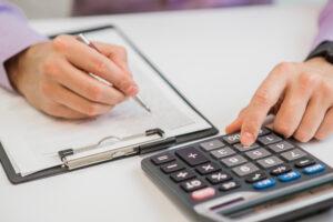 Contador anota dados de ativos em um papel na prancheta e digita valores em uma calculadora