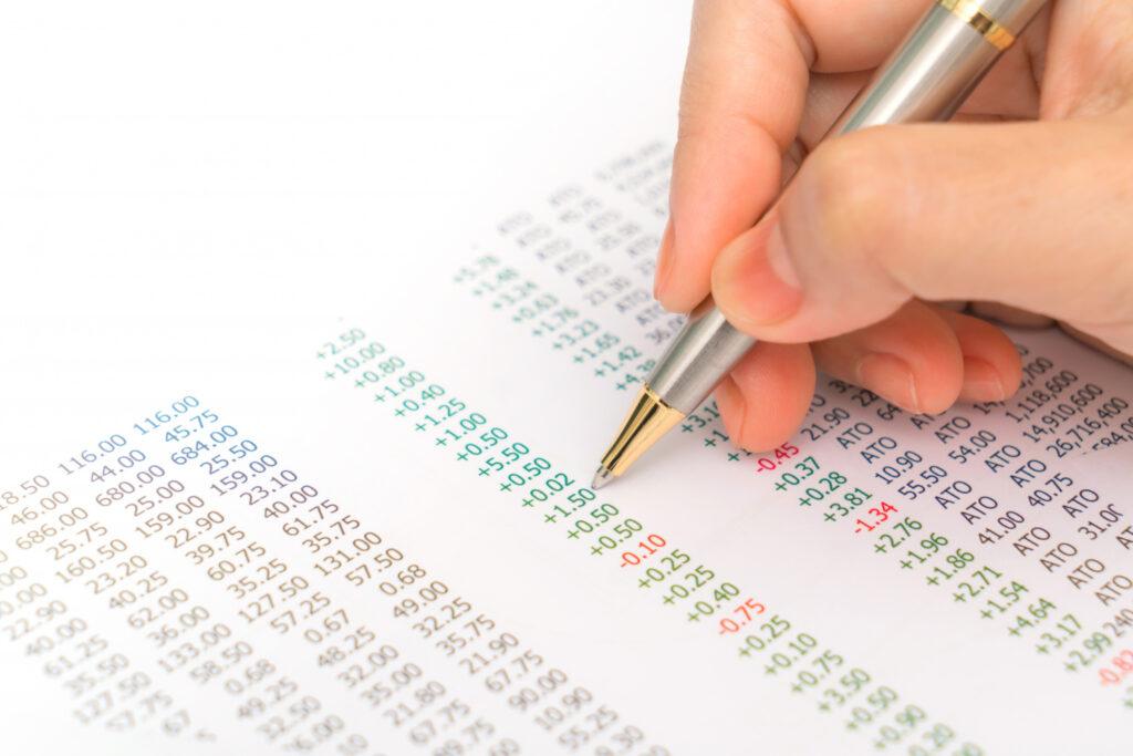 Mão segurando uma caneta calcula valores de números verdes e vermelhos descritos em um papel, mostrando a cobrança do come-cotas.