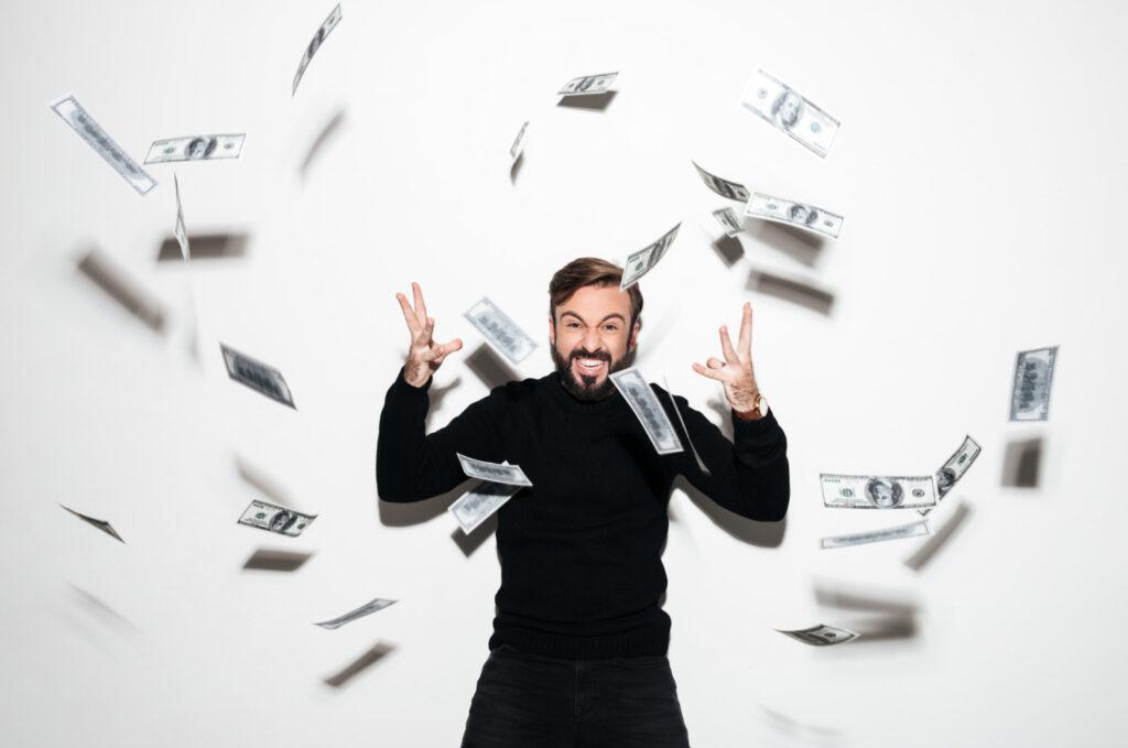 Homem aparece comemorando os ganhos de dividendos com uma chuva de dinheiro em volta dele