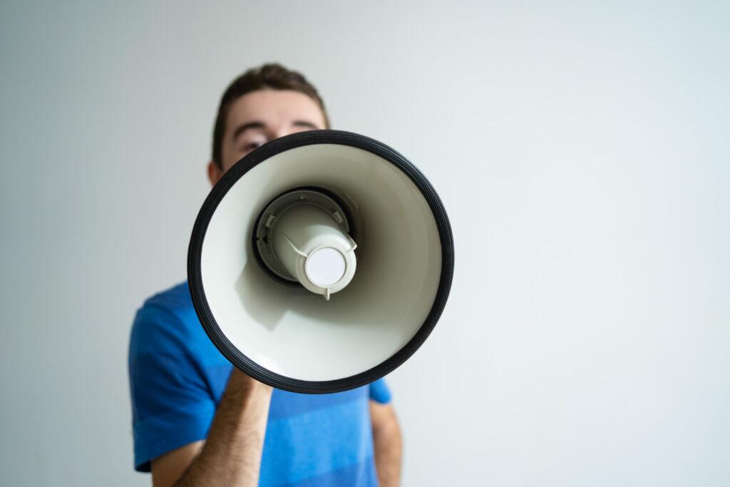 Homem aparece com um megafone gritando para informar um fato relevante