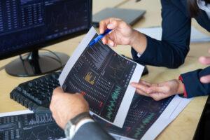 Mãos de executivos seguram uma caneta e um papel com vários gráficos do Ibovespa