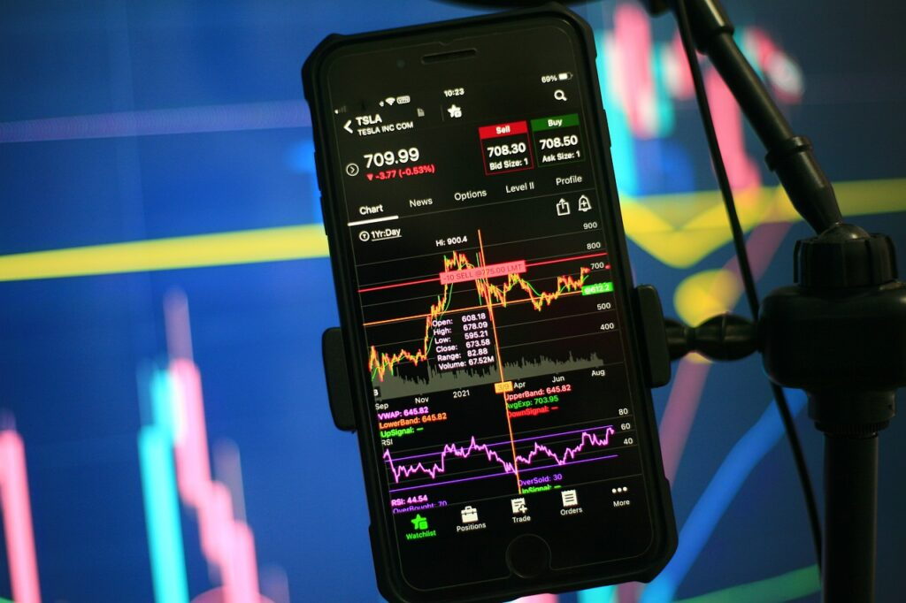 Celular com dados do mercado futuro aparece  na frente de uma tela com mais dados do mercado financeiro
