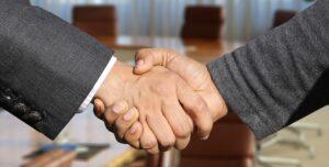 Duas mãos de executivos se cumprimentam para sinalizar o acordo de uma opção