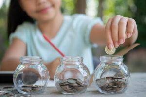 Menina asiática segura um lápis e coloca moedas em um dos três potinhos que aparece em sua frente para mostrar a diversificação possível com o perfil de investidor