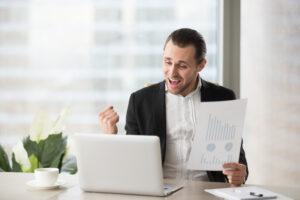 Executivo sentado à mesa em frente ao notebook segura uma folha de papel e comemora os ganhos de acordo com seu perfil de investidor