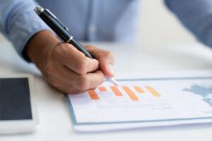 Executivo segura uma caneta e faz anotações em um papel com gráficos e informações de rating