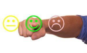 Uma carinha mediana, uma carinha sorridente e uma carinha triste aparecem e um dedo aponta para a carinha sorridente, mostrando o rating do emissor do título
