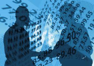 Investidores apertam as mãos com vários números aparecendo no fundo mostrando o tag along