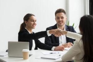 Executivos sentados em uma mesa apertam as mãos na negociação de um take over